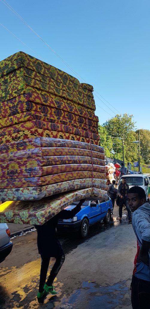 Junger Mann trägt eine große Anzahl von bunten Matratzen